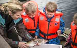 Two children and a woman looking at a cod